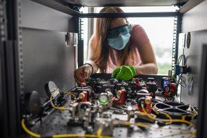 Eine Wissenschaftlerin macht letzte Einstellungen an der Laboraufbau.
